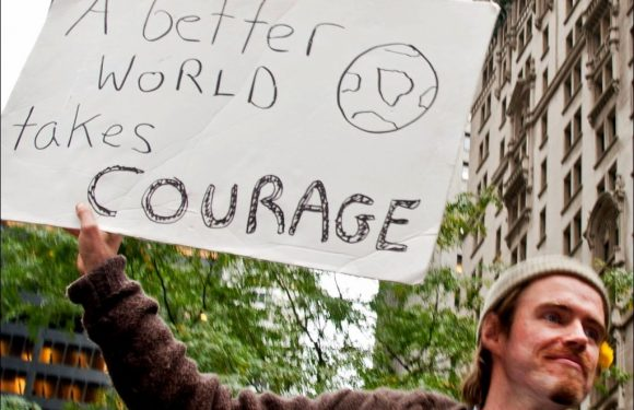 "Man with sign ""A Better World takes Courage"""