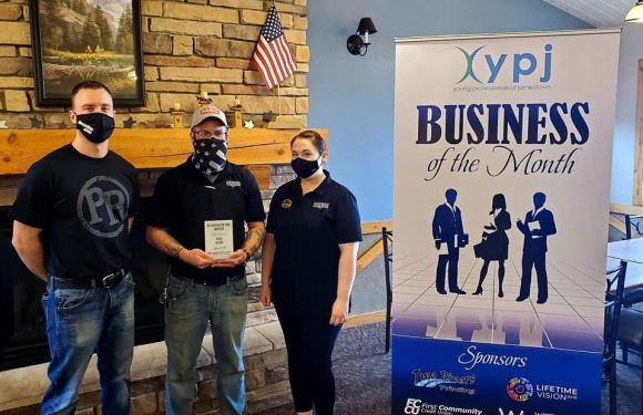 Pizza Ranch owner and managers holding award next to banner naming them Business of the Month winner.
