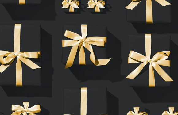 black wrapped gift boxes with gold bows lined in straight rows
