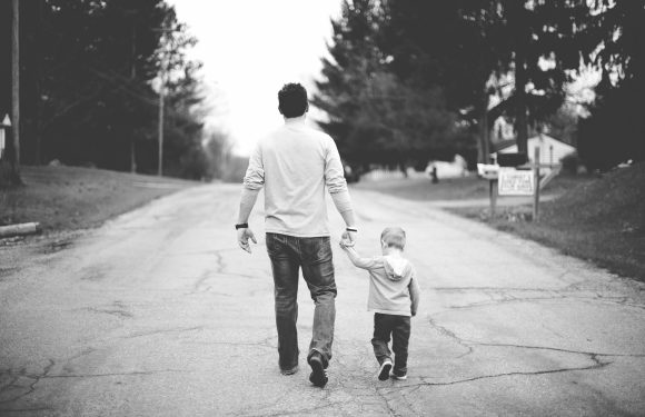 Black and white photo of father and young son holding hands and walking away down a paved residential road.