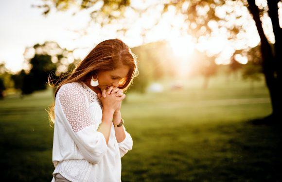Woman in prayer in open sunlight area