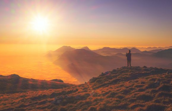 Person looking at a sunrise on a hills