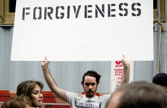 """Man holding a """"Forgiveness"""" sign and wearing a """"I'm Sorry"""" t-shirt"""