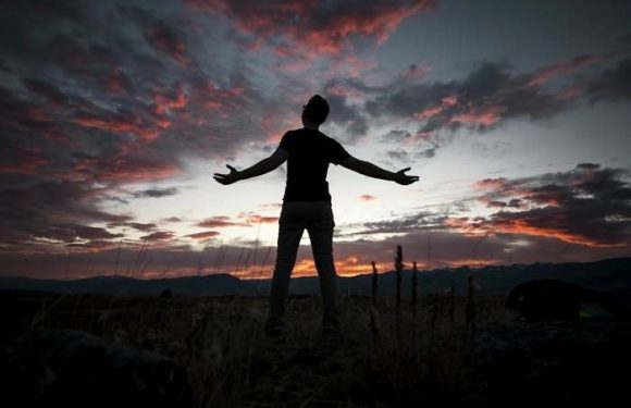 Silhouette of person with outstretched arms in front of sunset landscape