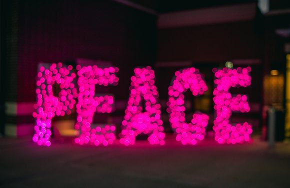 Blurry background of dark colors with peace word in pink bubble lights