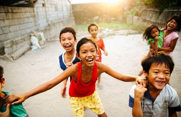 Kids smiling, playing, laughing, possibly in a 3rd world country