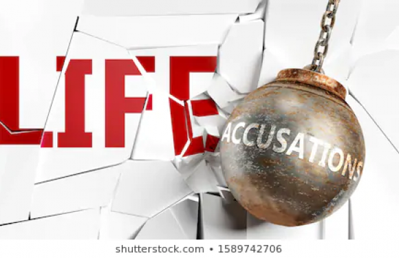 Wrecking ball with accusations written on it smashing mirror that says life