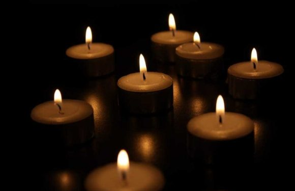 Individual candles lit in a dark room