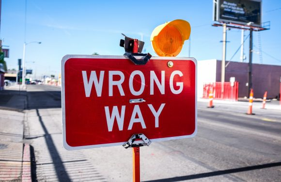 "Photo of a construction sign saying ""wrong way"" with a flashing light on it, traffic cones and street in the background."