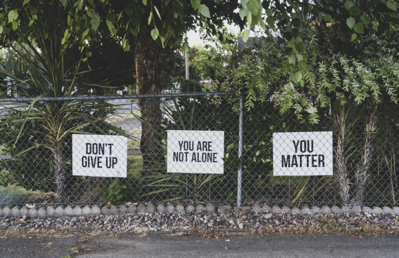 """Chainlink fence with encouraging posters saying """"Don't Give Up, You Matter, You are not alone"""" in front of trees"""