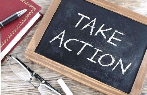 "Chalkboard with words ""Take action"" next to reading glasses, a pen and a notebook."