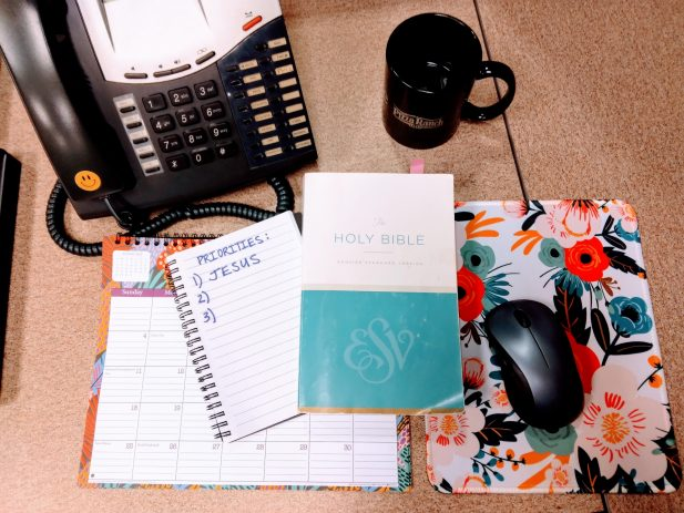 Office desk with phone, coffee mug, computer mouse, calendar, bible, and notebook with the words Priorities and number 1 says Jesus