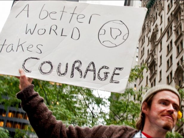 """Man with sign """"A Better World takes Courage"""""""
