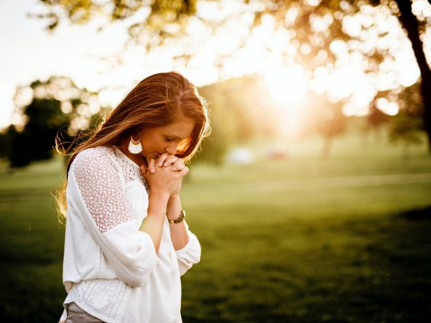 Woman in prayer in open sunlight area