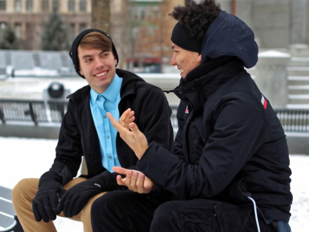 Two guys having a conversation on a park bench