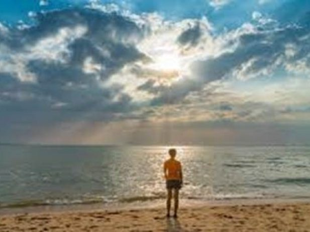 Person standing on the beach in front of the ocean with the sun shining through clouds in the background.