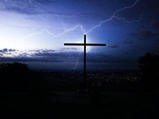 Thunderstorm landscape with cross in foreground