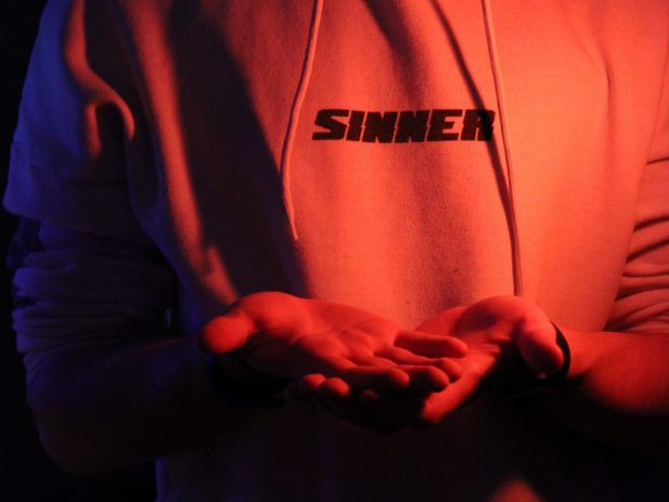 Person wearing a sweatshirt with the word sinner on the front