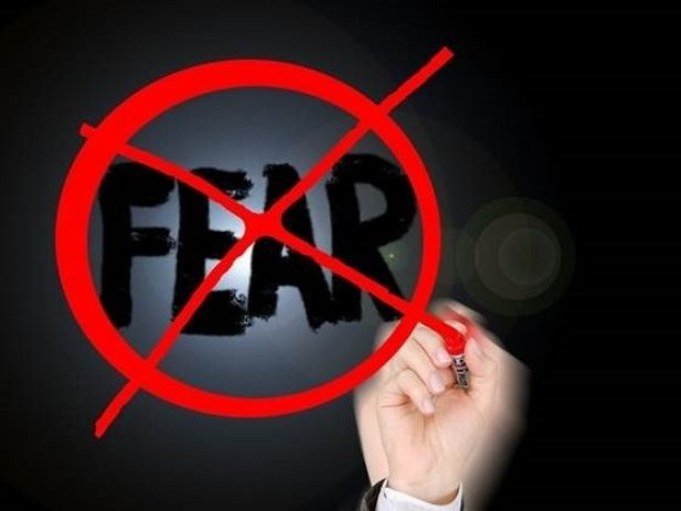 hand writing fear and crossing it out
