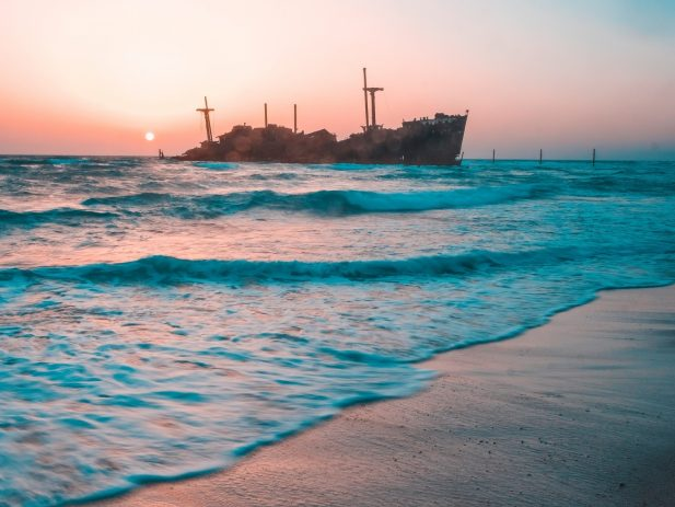 Ocean beach at sunset with wooden ship in background