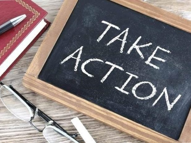 """Chalkboard with words """"Take action"""" next to reading glasses, a pen and a notebook."""