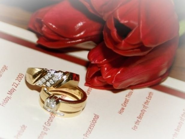Wedding rings and red tulips on top of Wedding program