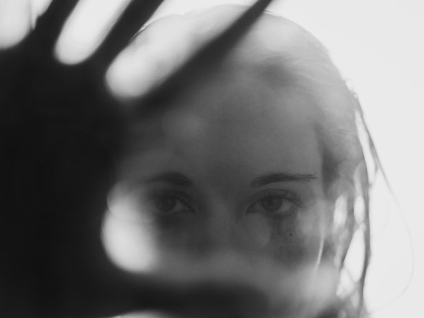 unfocused photo of woman holding hand up to camera lens