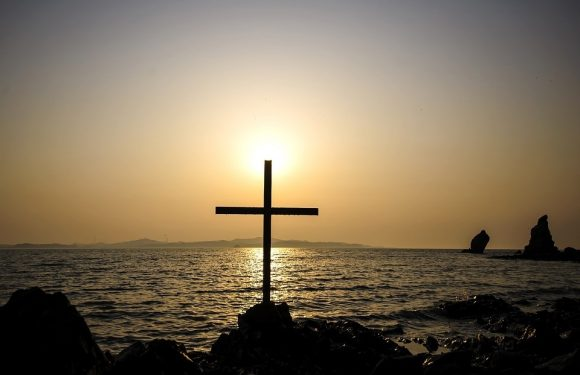 Cross near the sea with sun behind