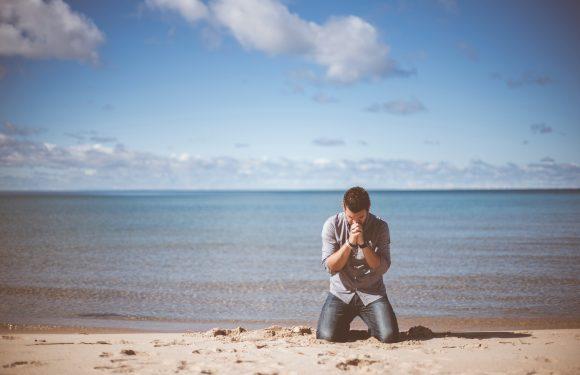 Man on beach praying