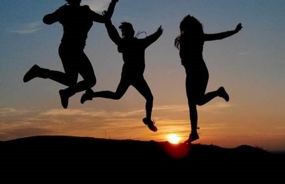 Silhouette of people jumping in front of a sunset