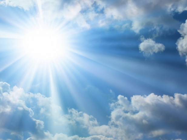 Bright sunlight with blue sky and fluffy white clouds