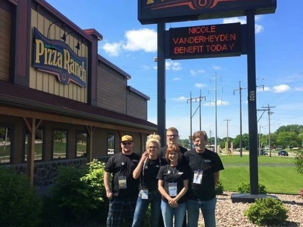 Pizza Ranch staff by their sign promoting the impact event