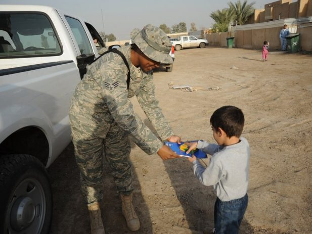 Army members giving crayons and coloring book to a little boy
