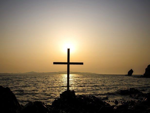 Cross near the sea with sun behind