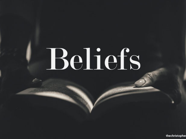 Person with open bible in lap with word beliefs in shadow
