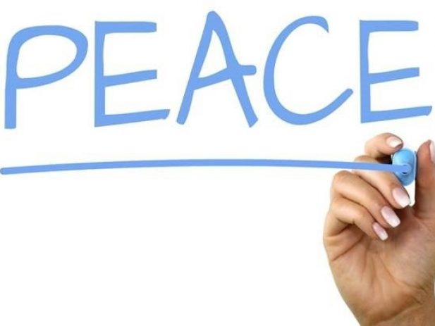 hand writing the word peace