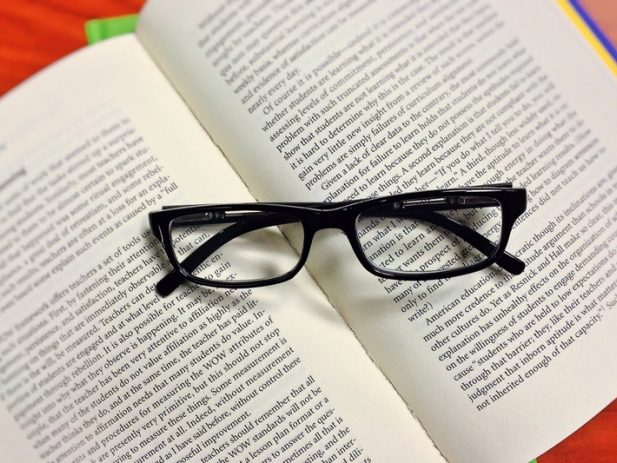 Open book with folded glasses on top