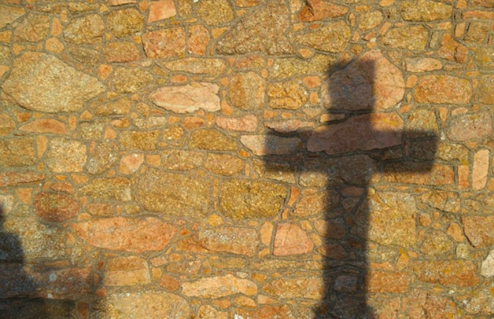 Shadow of a Cross on a Cobblestone Wall