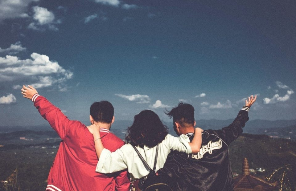 Three friends joyously looking over a hillside
